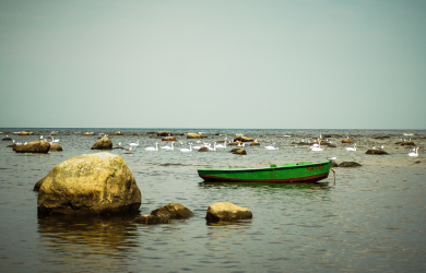 Green boat and rocks